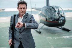 Businessman near private helicopter. Middle aged Businessman near helicopter Royalty Free Stock Images