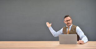 Middle-aged businessman orienting hand towards the wall Stock Photography