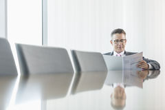 Middle-aged businessman reading book at conference table Stock Photo
