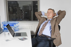 Middle-aged businessman resting on chair in front of laptop in office Stock Photo