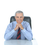 Middle aged Businessman seated a desk Royalty Free Stock Image