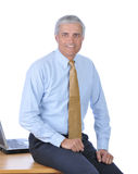 Middle Aged Businessman seated on his desk royalty free stock image