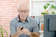 Middle Aged Businessman Sitting at Desk, with phone. Middle Aged Businessman Sitting at Desk, with cell phone royalty free stock photos