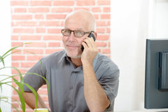 Middle Aged Businessman Sitting at Desk Talking on Stock Images