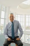 Middle aged Businessman on stool in office lobby Stock Photo