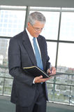 Middle aged Businessman Taking Notes Stock Photo