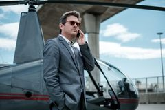Businessman talking on cellphone near private helicopter. Middle aged Businessman talking on cellphone near private helicopter Stock Photos