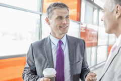Middle aged businessman talking with male colleague in railroad station Royalty Free Stock Images