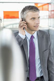 Middle aged businessman using cell phone at train station Royalty Free Stock Image