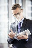 Middle aged businessman using digital tablet in office Royalty Free Stock Image