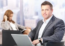 Middle-aged businessman using laptop in hall stock images