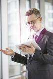 Middle aged businessman using tablet PC in office Royalty Free Stock Photos