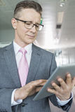 Middle-aged businessman using tablet PC in office Royalty Free Stock Image
