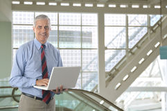 Middle aged Businessman with White laptop Stock Photography