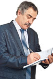 Middle aged businessman writing in agenda Royalty Free Stock Photography