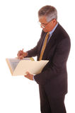 Middle aged Businessman Writing in Folder Stock Photos