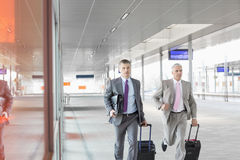 Middle aged businessmen with luggage rushing on railroad platform Royalty Free Stock Images