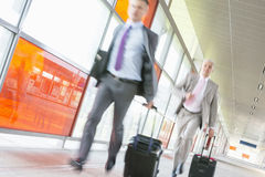 Middle aged businessmen with luggage rushing on railroad platform Royalty Free Stock Image