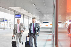 Middle aged businessmen with luggage rushing on railroad platform Stock Images