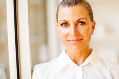 Middle aged businesswoman. Elegant middle aged businesswoman closeup portrait in office stock image