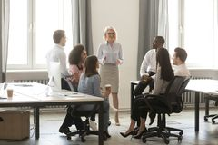 Middle aged businesswoman boss mentor training interns employees in office stock images