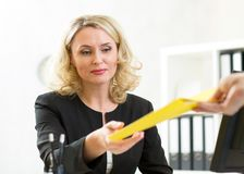 Middle-aged businesswoman giving paper to Royalty Free Stock Photography