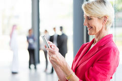 Middle aged businesswoman reading email. Beautiful middle aged businesswoman reading email on smart phone Royalty Free Stock Photography