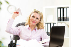 Middle-aged businesswoman throwing paper airplane Stock Photos