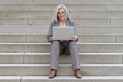 Middle-aged businesswoman using her laptop in town stock images