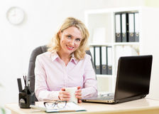 Middle aged businesswoman working on laptop and drinking coffee Royalty Free Stock Photos