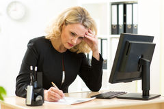 Middle-aged businesswoman working in office and examining reports stock image