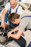 Middle aged car repairman helping colleague Stock Image