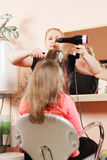 Hairdo. Middle-aged caucasian female stylist at hairdo process Stock Photos