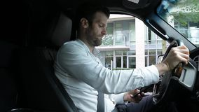 A middle aged caucasian man distracted driving while using a mobile device stops his vehicle suddenly to avoid an