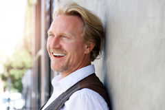 Middle aged caucasian man leaning to wall and laughing Stock Image