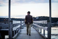 Middle aged caucasian man walking on a pier wearing a blazer and a top hat shot from behind royalty free stock photography