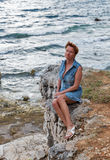 Middle aged caucasian tanned woman on the rocky sea beach Stock Images