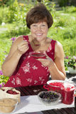 Middle aged Caucasian woman with raspberry jam Stock Photos