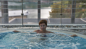 Middle aged Caucasian woman relaxing in jacuzzi Stock Photo