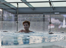 Middle aged Caucasian woman relaxing in jacuzzi Stock Images