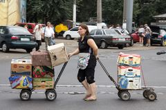Middle aged caucasian woman showing efforts pulling a cart in the privoz central market of Odessa. Picture of the privoz Markey, with one white caucasian female stock images