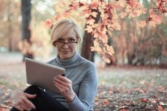 Middle aged caucasian woman sits alone at golden autumn park with tablet, smiling. Casual wear, glasses. Precious age concept. royalty free stock image