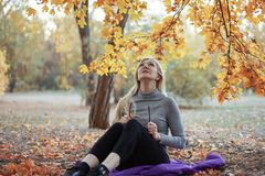 Middle aged caucasian woman sits alone at golden autumn park with tablet, smiling. Casual wear, glasses. Precious age concept. stock photo