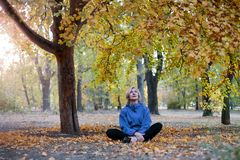 Middle aged caucasian woman sits alone under the big tree at autumn park. Bright casual wear, white wireless earphones, meditation stock photos