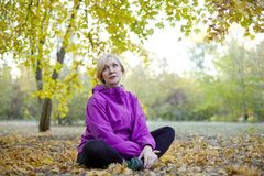 Middle aged caucasian woman sits alone under the big tree at autumn park. Bright casual wear, white wireless earphones, meditation royalty free stock photography