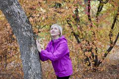 Middle aged caucasian woman stands alone near to the tree at autumn park. Hands on the tree, bright casual wear, white wireless ea royalty free stock photography