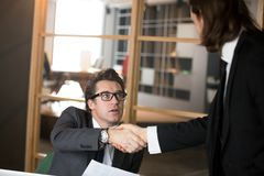 Middle aged CEO shaking hand of new millennial company worker stock photos