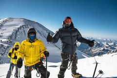 A middle-aged climber in a down jacket and harness shows a thumb up next to his friends on the way to the top of a snow. Capped mountain. The concept of rest Stock Photos