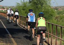 Middle aged co-ed bike ride. Five middle aged men and one middle aged woman with helments, biker shorts, and jerseys ride bycicles during their weekend ride stock image
