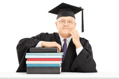 Middle aged college professor posing with a stack of books Stock Photos